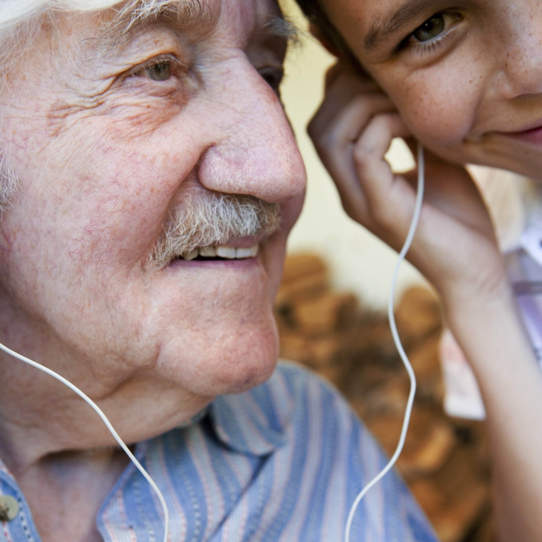 Elderly Man Listening to Music with Grandson