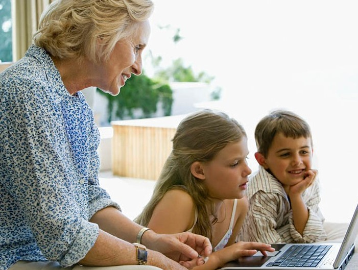 Children and grandparent using laptop computer
