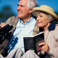 Senior couple holding binoculars and a book