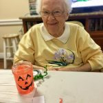 Shirley and her almost-finished pumpkin smiling for a picture!