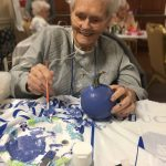 Dorothy smiling as she paints a periwinkle pumpkin!