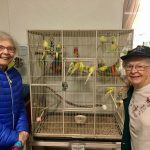 Audrey and Shirley smile next to a family of yellow parakeets!
