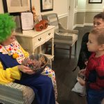 Shirley the clown with a line of candy-seeking little ones!