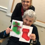 Community Life Assistant Sterling poses with Lily who proudly displays her finished greeting cards!