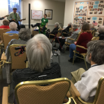 Big crowd at the at the St. Patty's Day party featuring a live musical performance by Willie & Jan Nininger, accompanied by Diana and a dancing leprechaun!